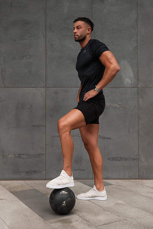Mark melbournes mediteranian fitness model standing with his foot on a medicine ball