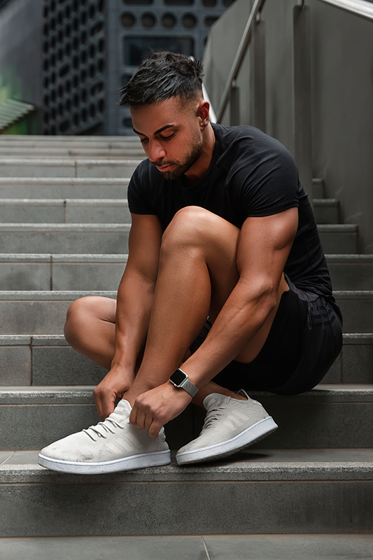 Mark melbournes mediteranian fitness model tying his shoe lace