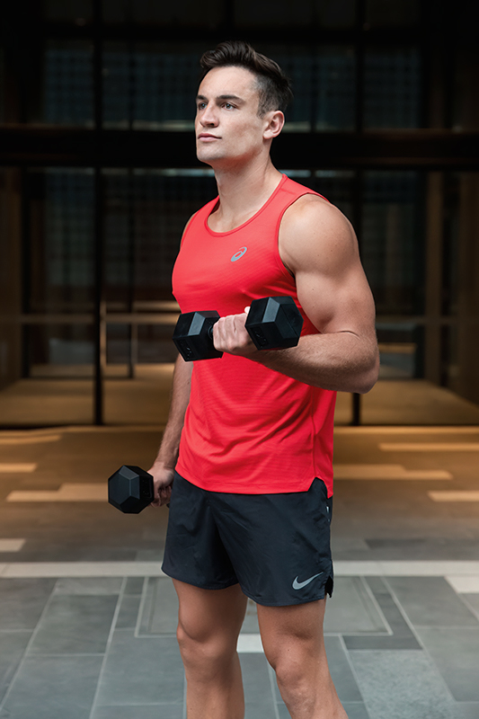 Mitchell ex Melbourne AFL star curling a dumbbell