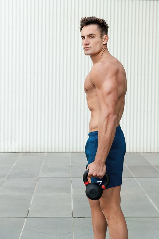 Mitchell ex Melbourne AFL star side image holding a dumbbell