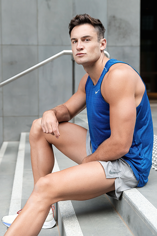 Mitchell ex Melbourne AFL star sitting casually on a stairwell