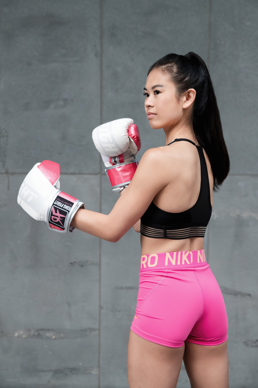 Katherine Melbourne based balinese fitness model in a boxing stance wearing white boxing gloves