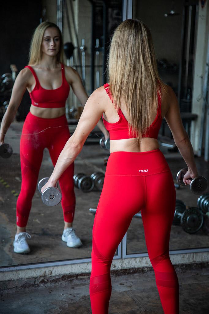 Melbourne fitness model dancer leaning against the dumbbell rack