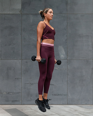Isabella H Melbourne Australia Elite Fitness Model jumping with a set of dumbbells