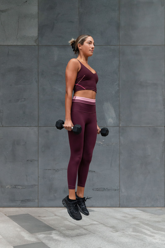 Isabella H Melbourne Australia Elite Fitness Model power jumpng with dumbbells