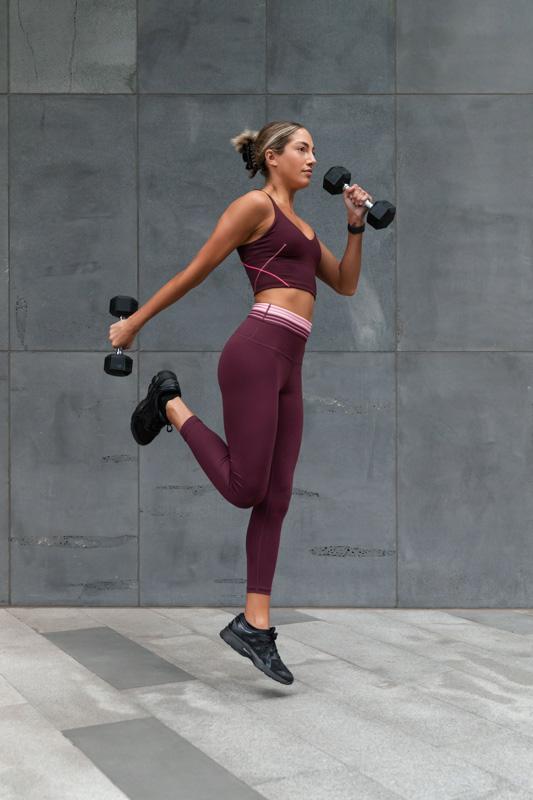 Isabella H Melbourne Australia Elite Fitness Model running with dumbbells in hand
