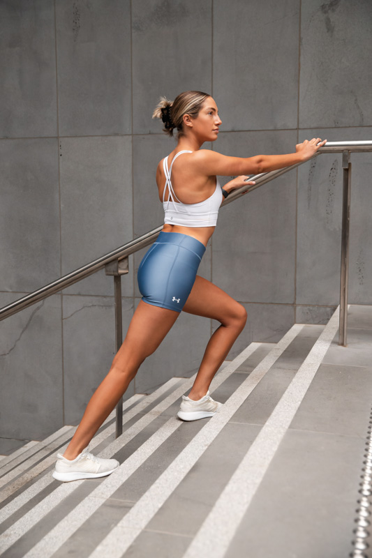 Isabella H Melbourne Australia Elite Fitness Model stretching against a stair rail
