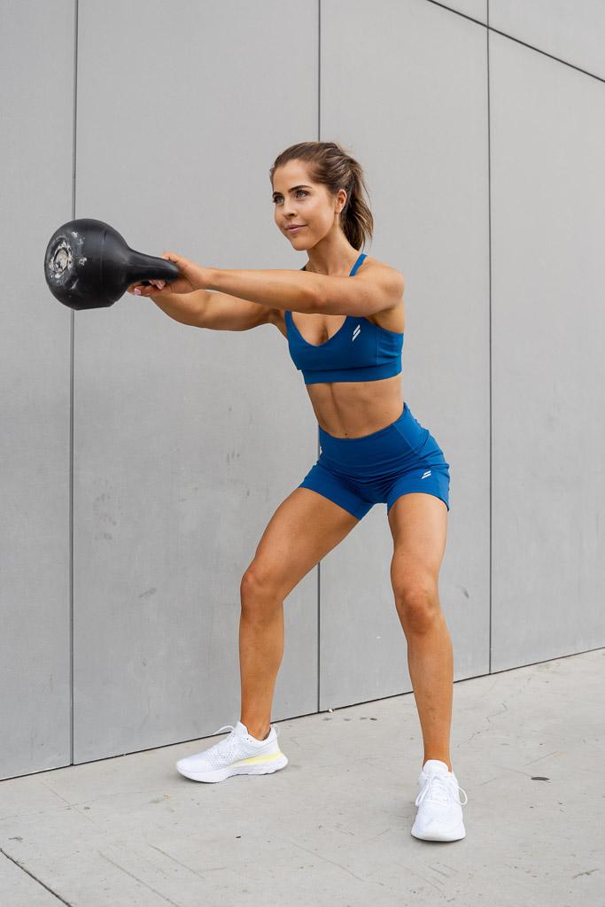 Natasha Australia Elite blonde fitness model doing kettlebell swing throughs
