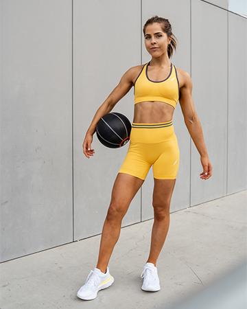 Natasha Australia Elite blonde fitness model holding a medicine ball
