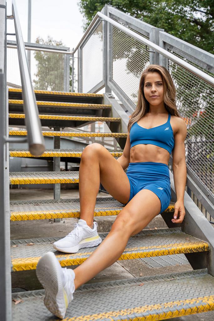 Natasha Australia Elite blonde fitness model sitting on a stairwell