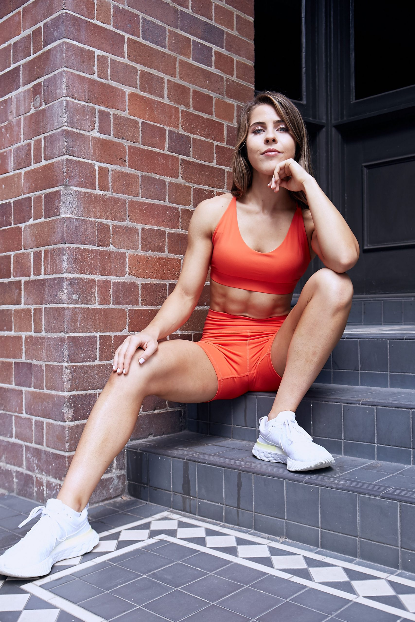 Natasha Sydney female fitness model and athlete sat in the dorrway during her fitness photo shoot scaled