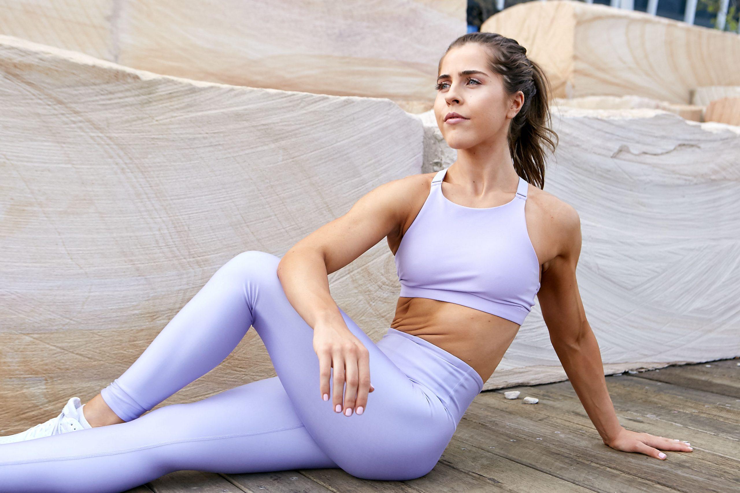 Natasha Sydney female fitness model and athlete seated stretching scaled