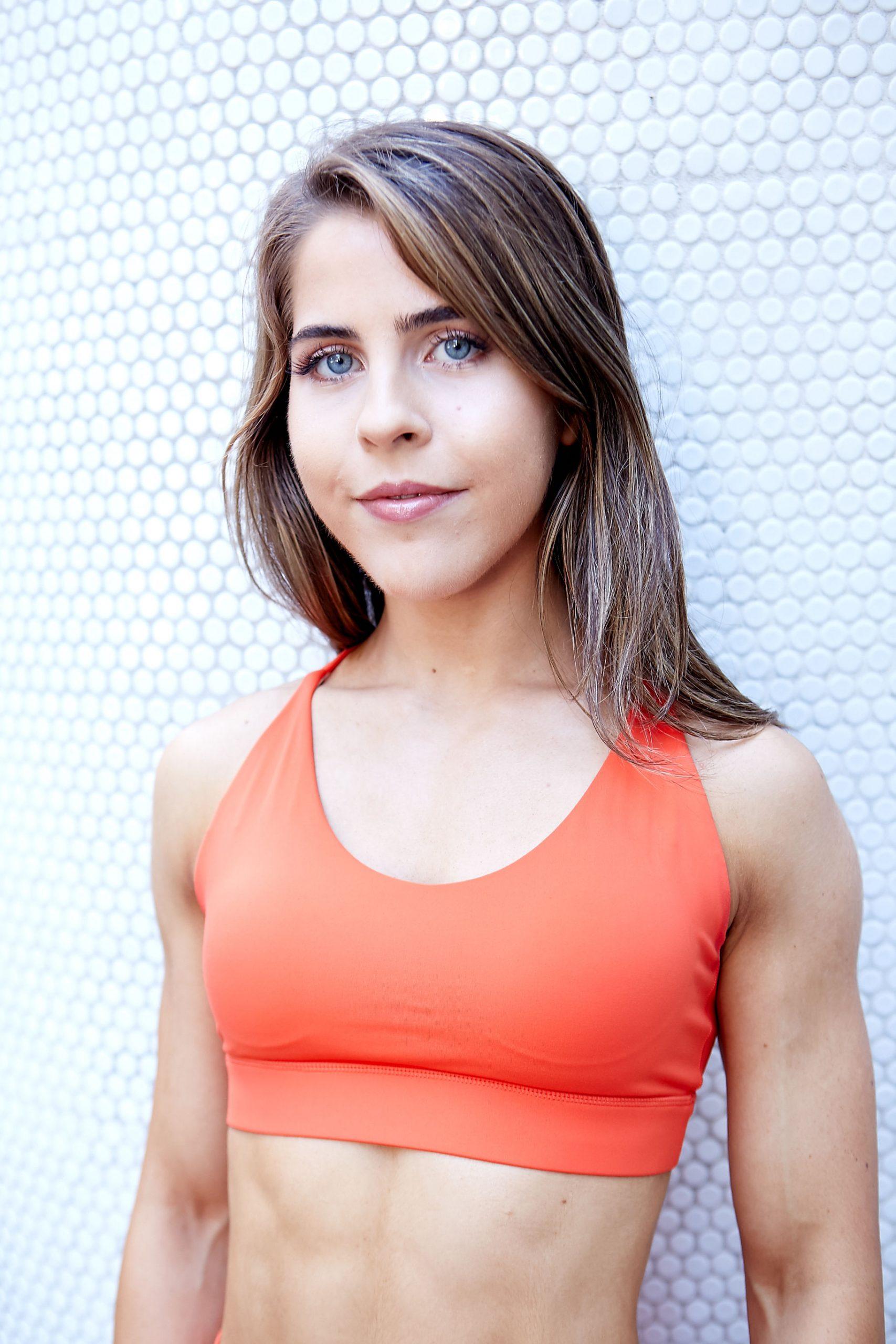 Natasha Sydney female fitness model and athlete wearing orange nike top during photo shoot scaled
