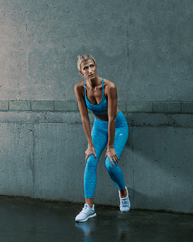 Samantha Sydney personal trainer fitness model leaning against the wall