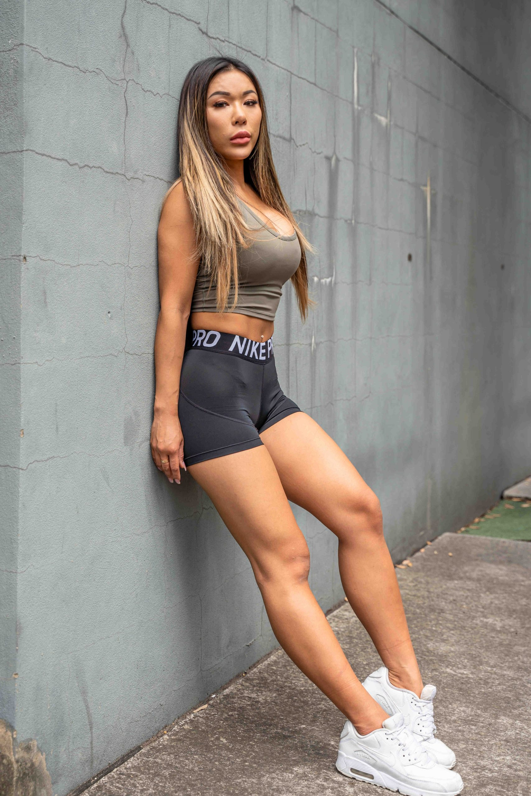 Zora Sydneys chinese fitness model leaning against the wall scaled